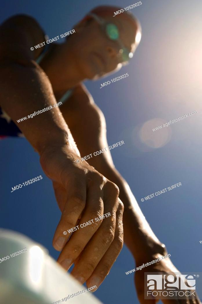 Stock Photo: Female swimmer on starting blocks focus on hands low angle view.