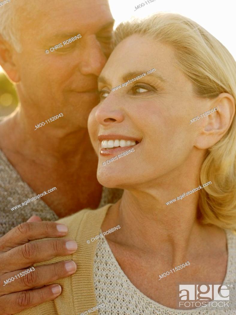 Stock Photo: Senior couple embracing at sunset close up.