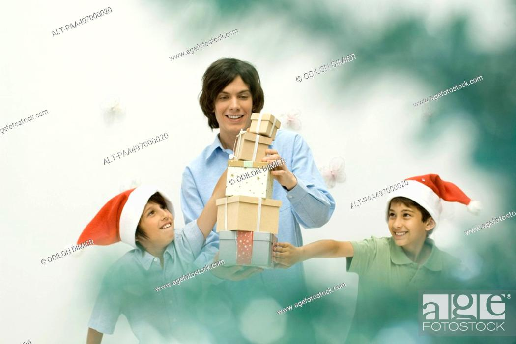 Stock Photo: Three brothers stacking Christmas gifts, smiling, selective focus.