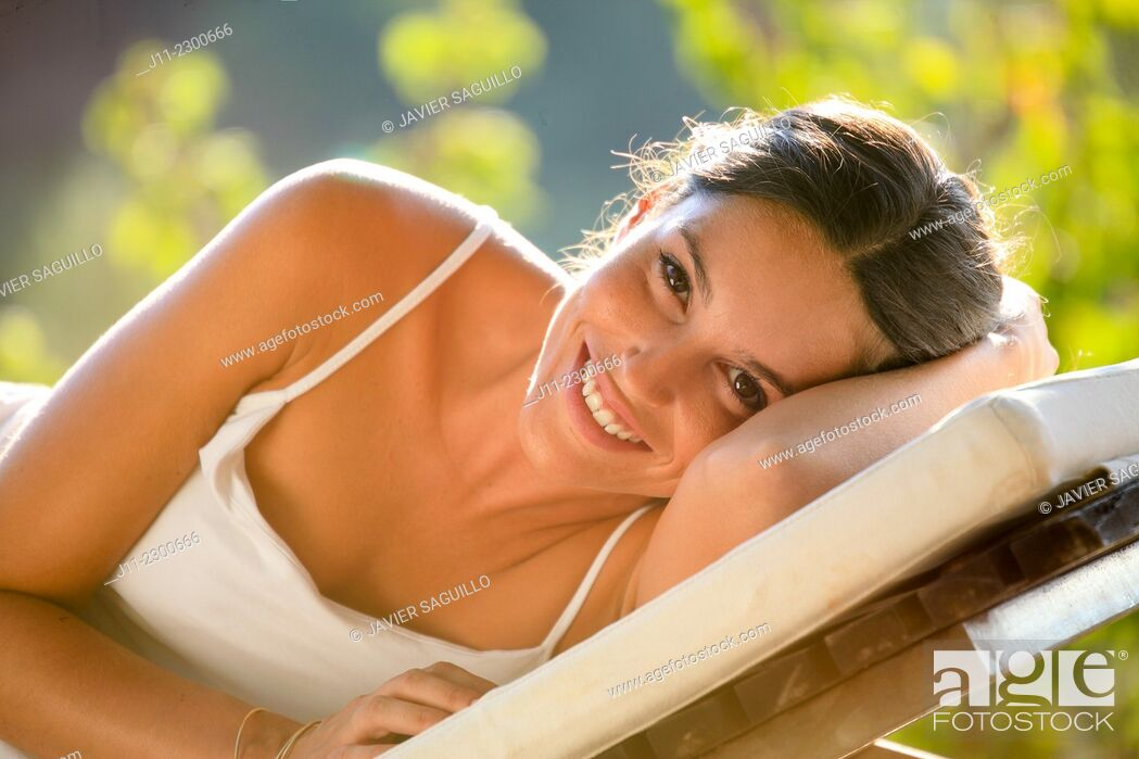 Stock Photo: Woman lying down on sunlounger.