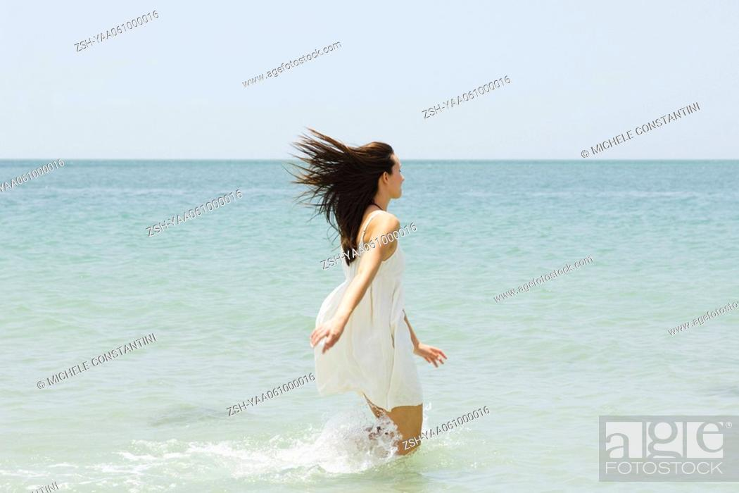 Stock Photo: Young woman at the beach, running knee deep in water, rear view.