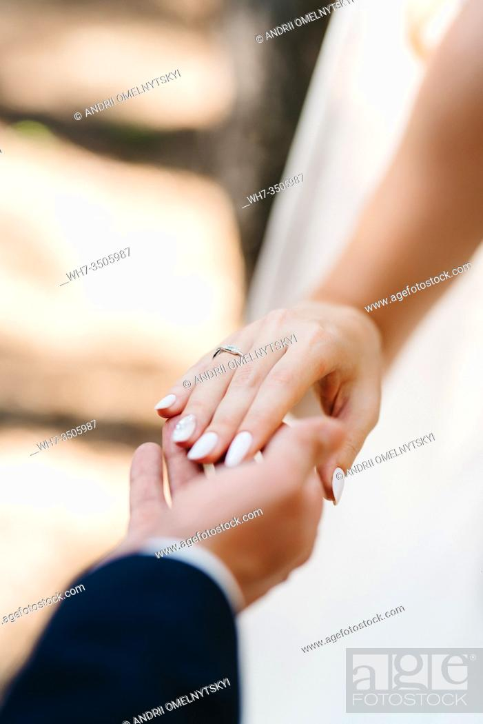 Stock Photo: the bride and groom tenderly hold hands between them love and relationships.