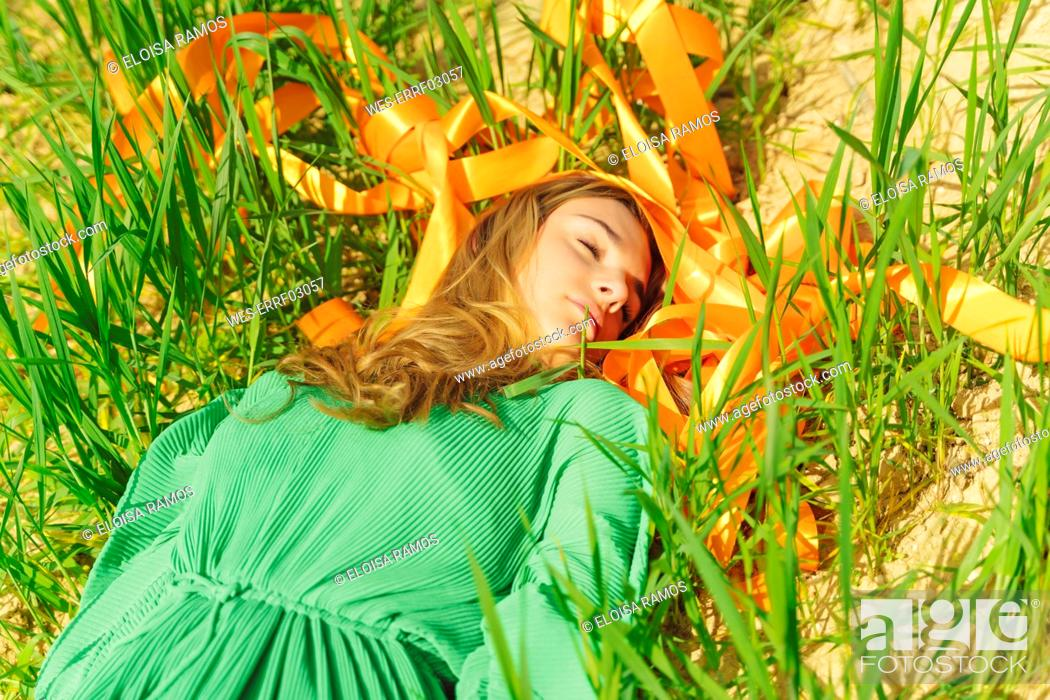 Stock Photo: Young woman with closed eyes lying in a field with orange ribbons.