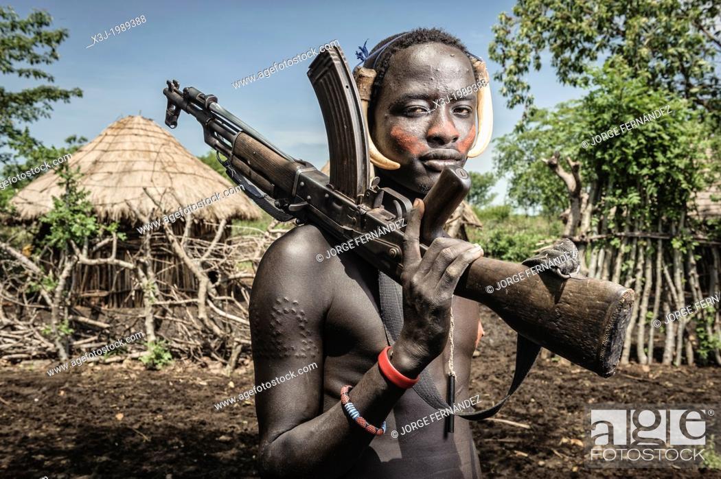 Stock Photo: Portrait of a young mursi man holding a kalashnikov, Omo valley, Ethiopia.