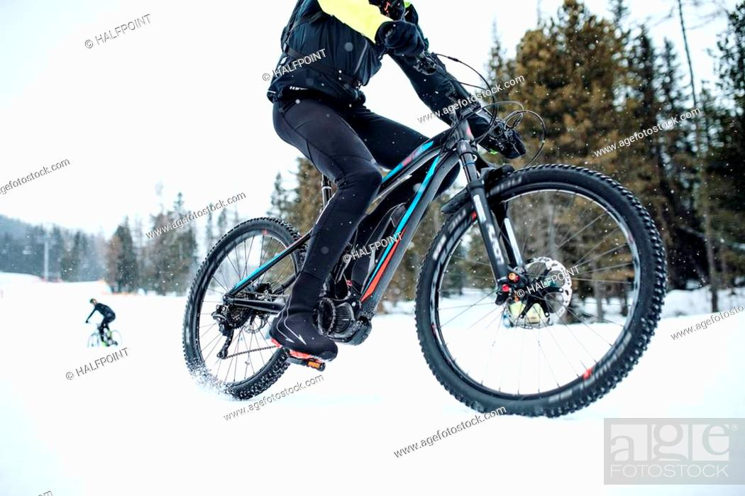Stock Photo: A midsection of mountain biker riding in snow outdoors in winter.