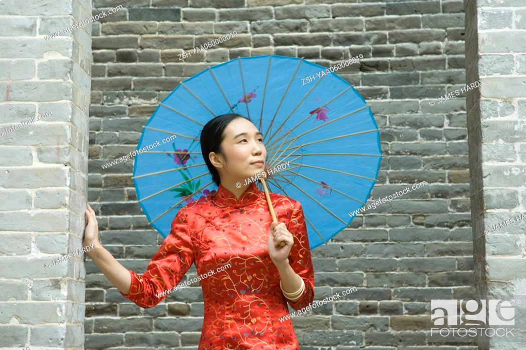 Stock Photo: Young woman dressed in traditional Chinese clothing, standing under parasol, looking up.