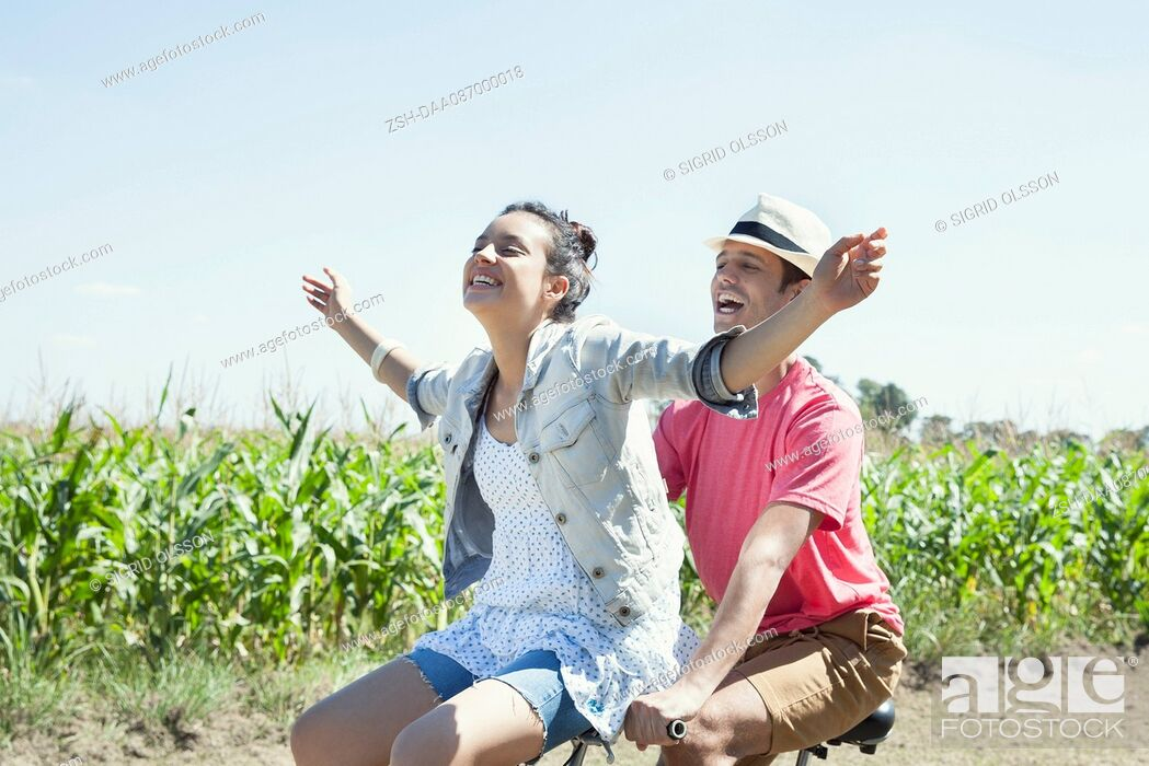 Stock Photo: Couple riding bike together, woman with arms outstretched.