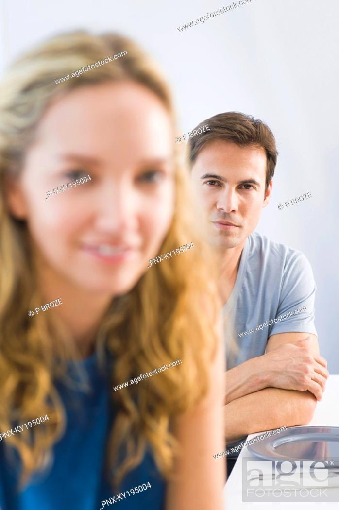 Stock Photo: Portrait of a man and a woman sitting at a dining table.