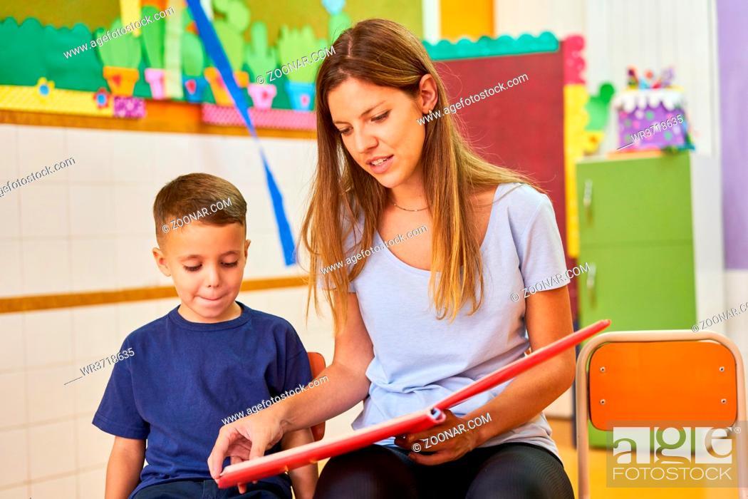 Stock Photo: Erzieherin oder Tagesmutter mit Kind beim Buch vorlesen im Kindergarten oder Hort.