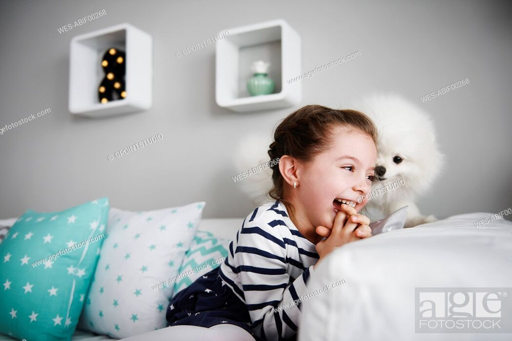 Stock Photo: Laughing little girl playing with dog on the couch in the living room.