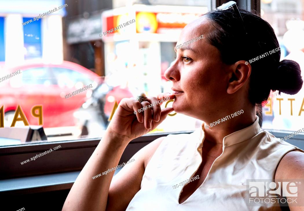 Stock Photo: Businesswoman with hand on chin in coffee bar.