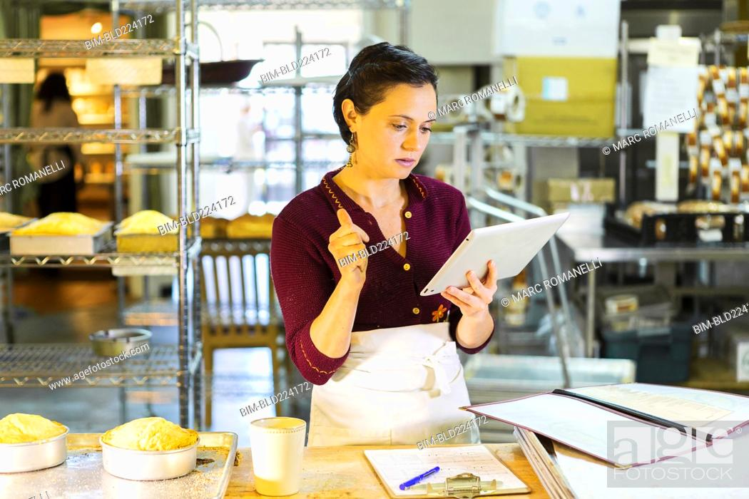 Stock Photo: Caucasian woman using digital tablet in bakery.