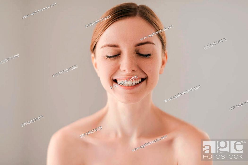 Stock Photo: Sincere smile. Portrait of gorgeous young woman with freckles on face smiling and keeping eyes closed while standing against grey background.