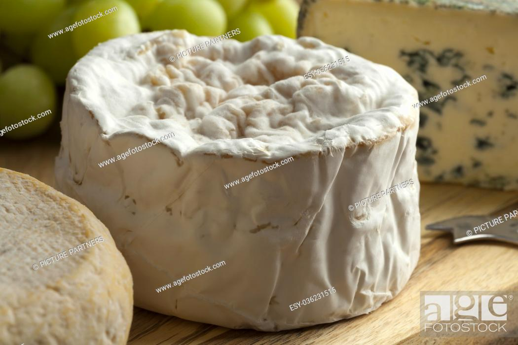 Photo de stock: Small camembert cheese close up on a french cheese board.