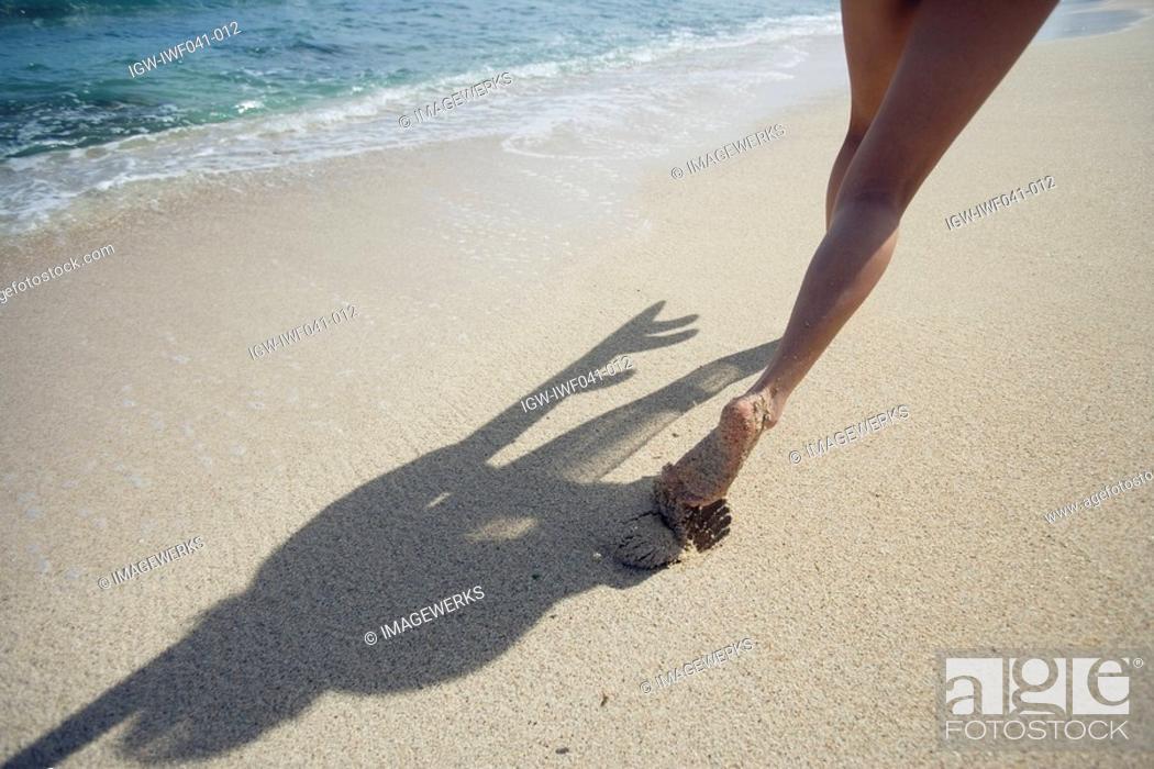 Stock Photo: A woman strolling on beach.