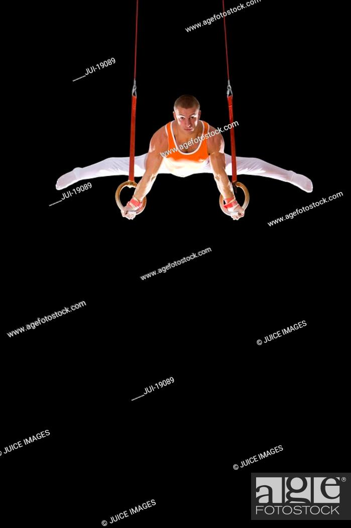 Stock Photo: Male gymnast performing on gymnastic rings, portrait, low angle view.