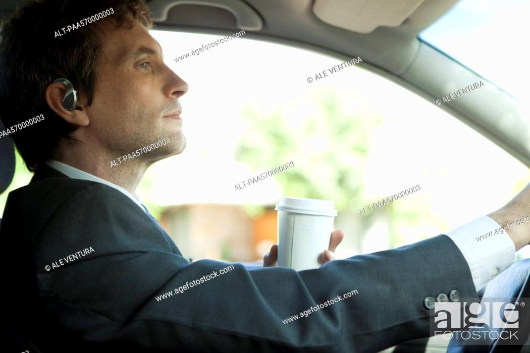Stock Photo: Businessman driving to work with cup of coffee in hand.
