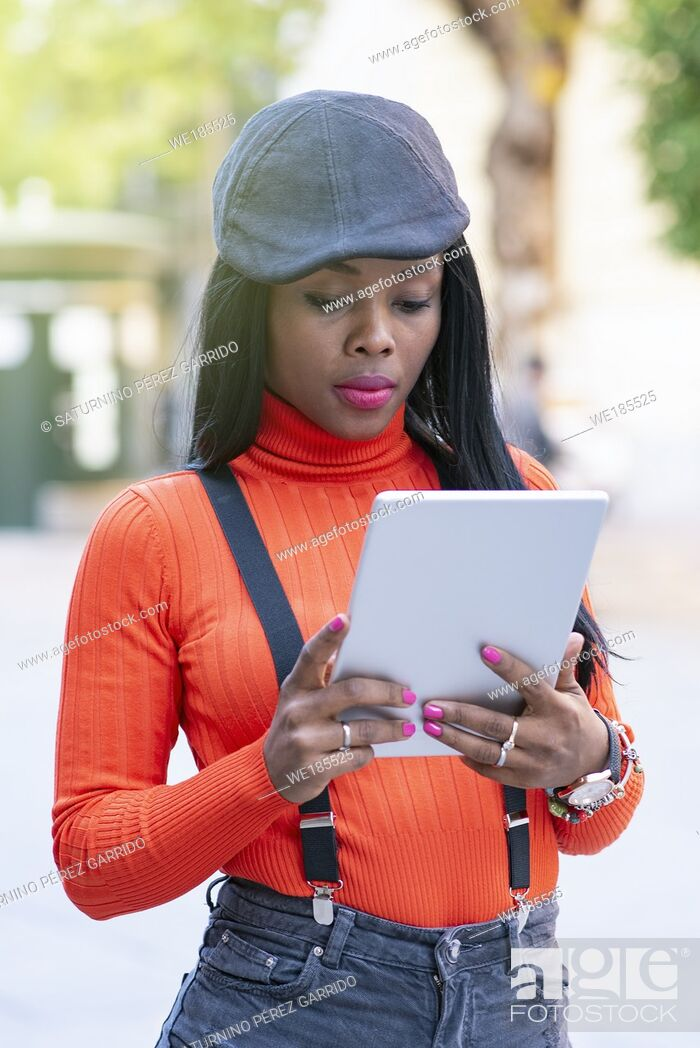Stock Photo: Beautiful young woman with dark skin using a tablet in the middle of the street.