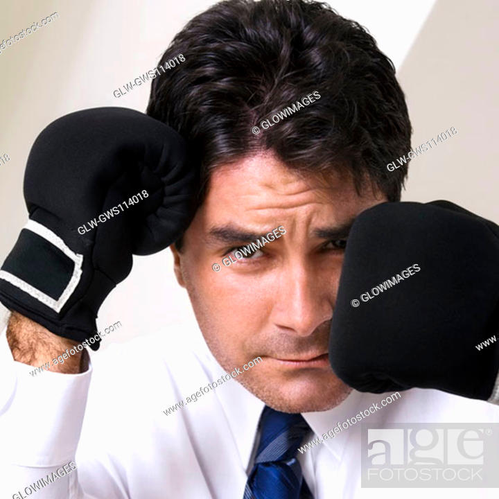 Stock Photo: Portrait of a businessman wearing boxing gloves.