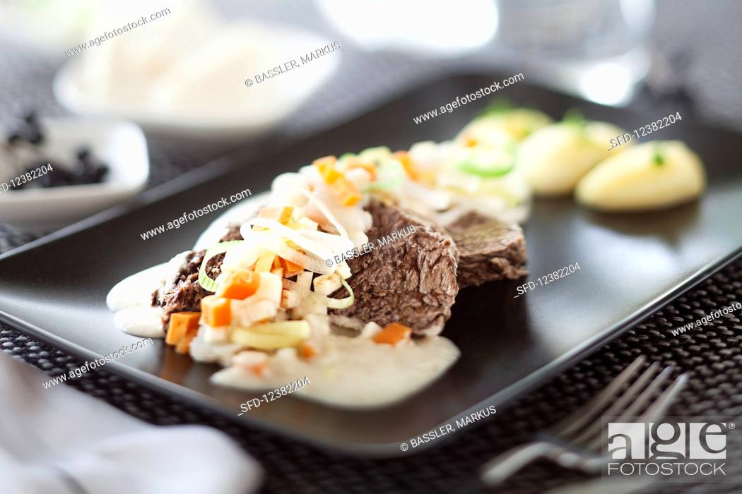 Stock Photo: A joint of prime boiled beef with vegetables, horseradish sauce and potatoes.
