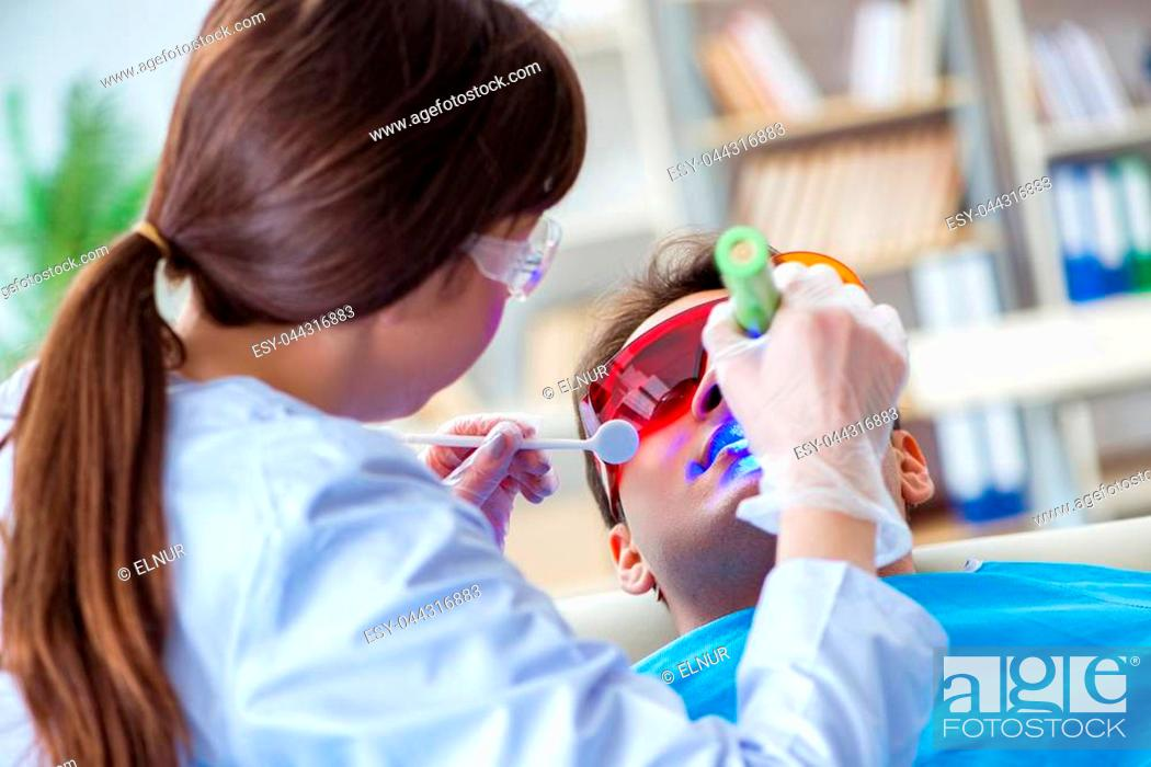 Stock Photo: Woman dentist doctor with male patient in hospital.