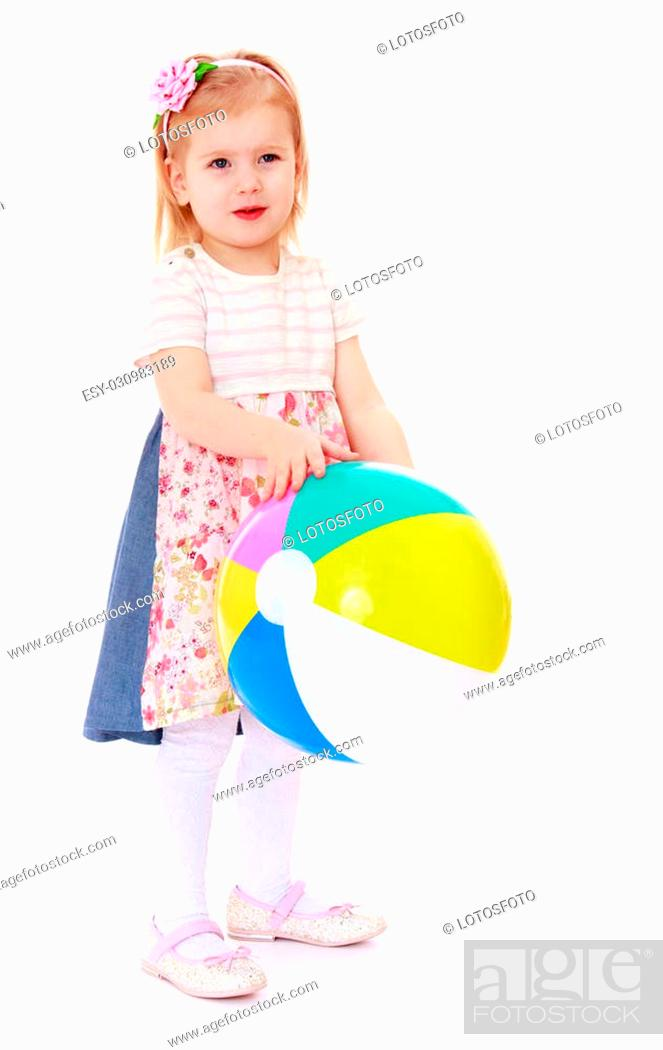 6893de5fa Stock Photo - Adorable little blonde girl in a long dress holding a front  of a big striped beach ball-Isolated on white
