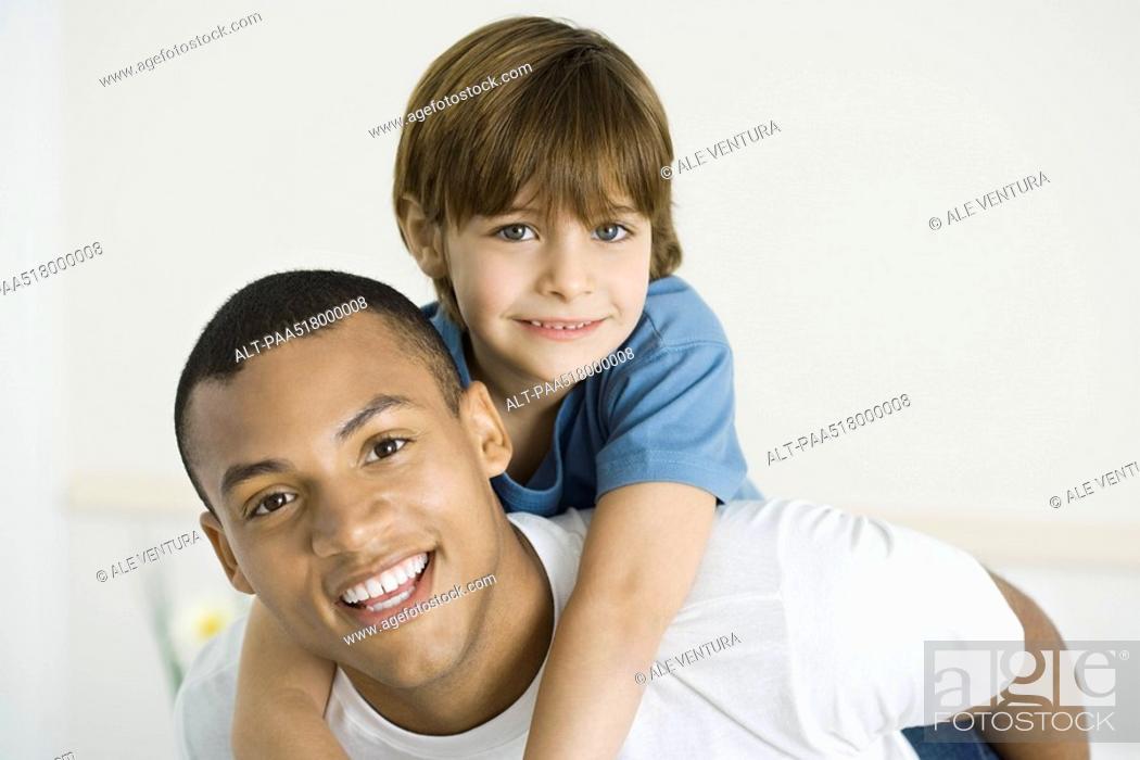 Stock Photo: Young man giving boy piggyback ride, both smiling at camera.