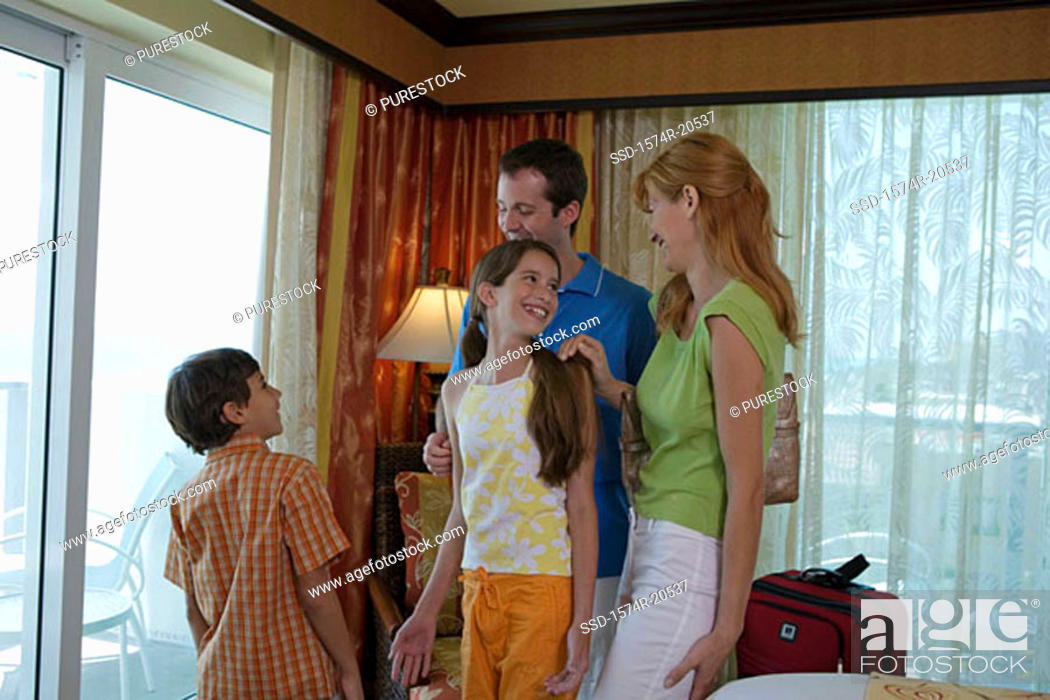 Stock Photo: Young couple standing with their son and daughter in a hotel room.