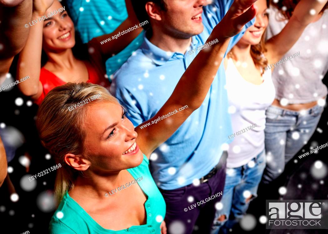 Stock Photo: party, holidays, celebration, nightlife and people concept - smiling friends waving hands at concert in club and snow effect.
