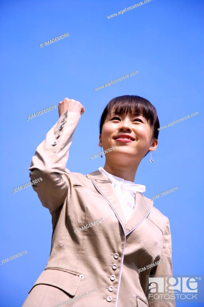 Stock Photo: Young woman smiling with fists up and looking up with confidence.