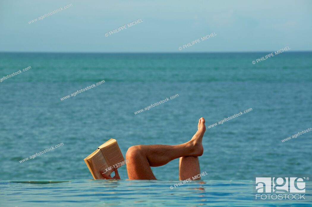 Stock Photo: Thailand, Siam gulf, Ko Samui island, man reading book at the swimming pool.