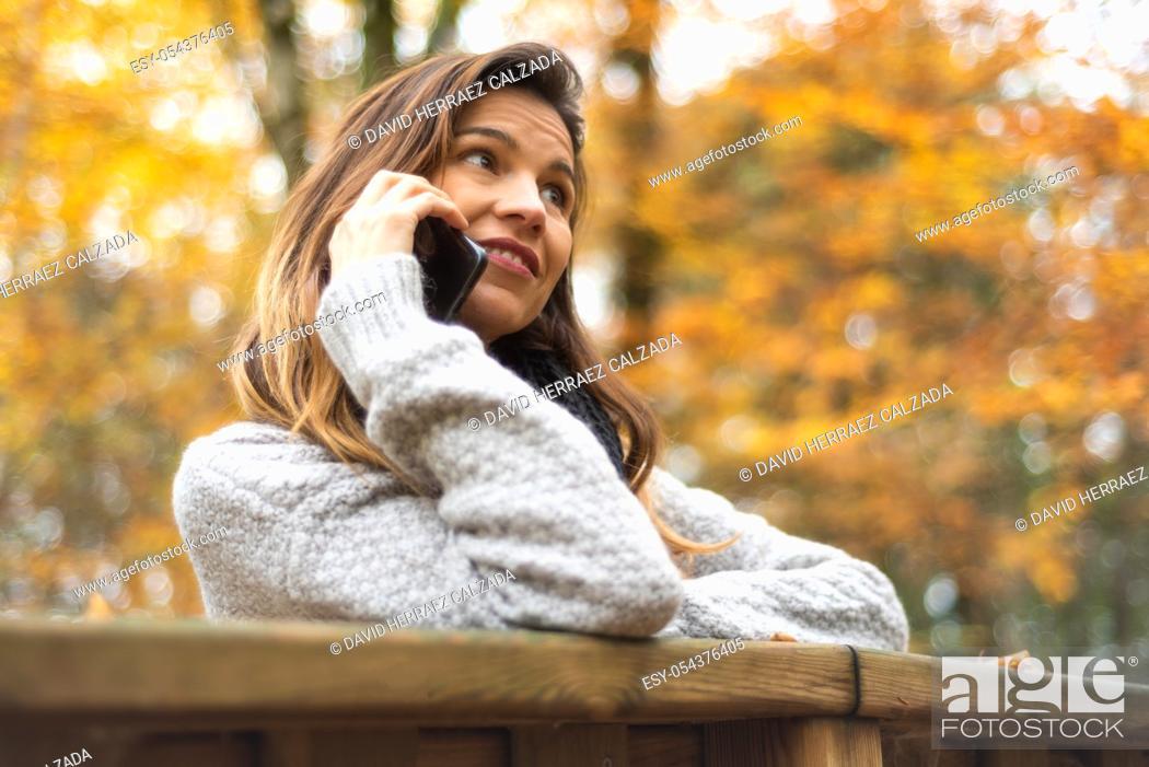 Stock Photo: Smart phone Autumn woman talking on mobile phone in fall. Autumn girl having smartphone conversation in sun flare foliage.
