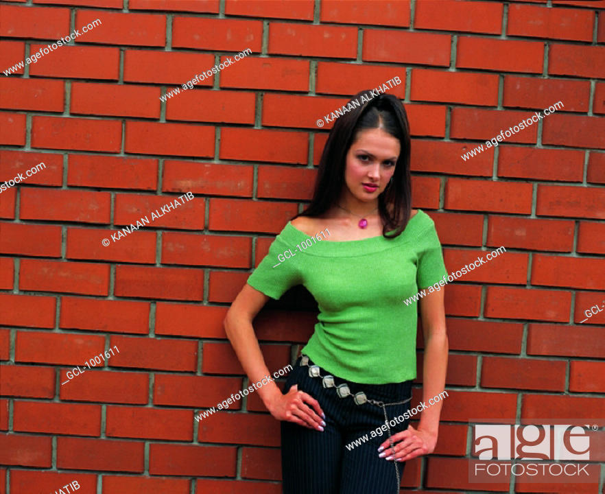Stock Photo: Woman standing at a wall.
