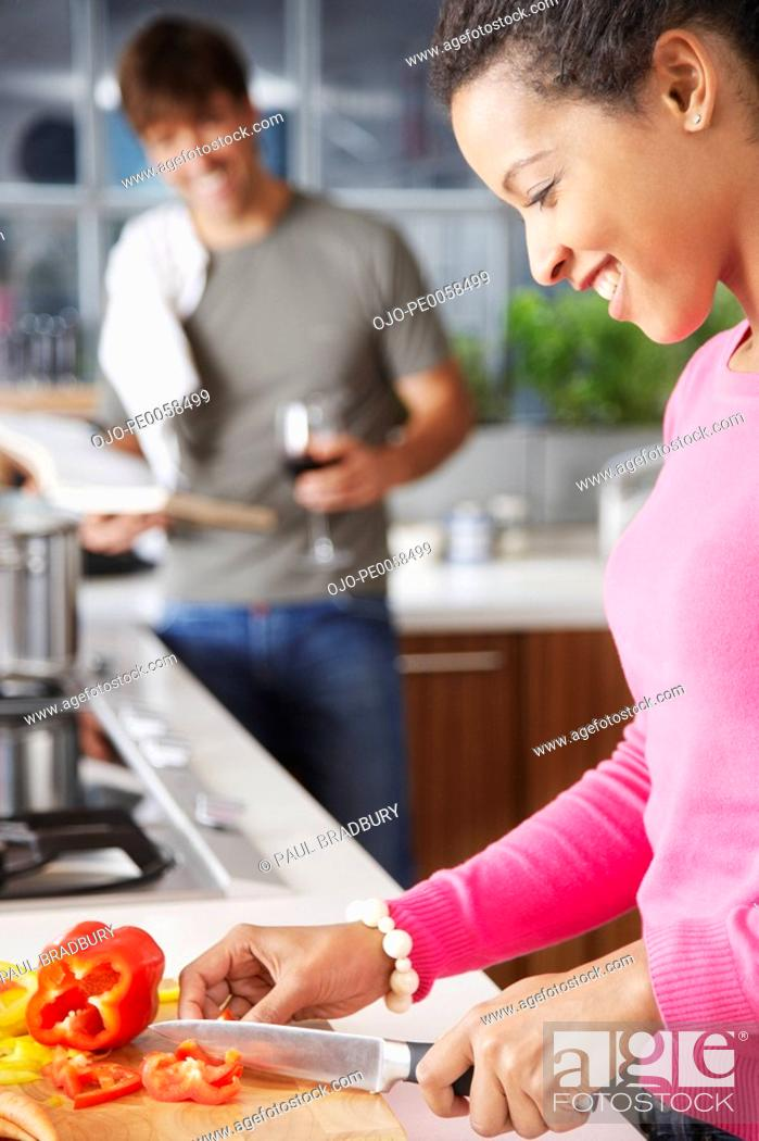 Stock Photo: Woman cutting red peppers with man in background.