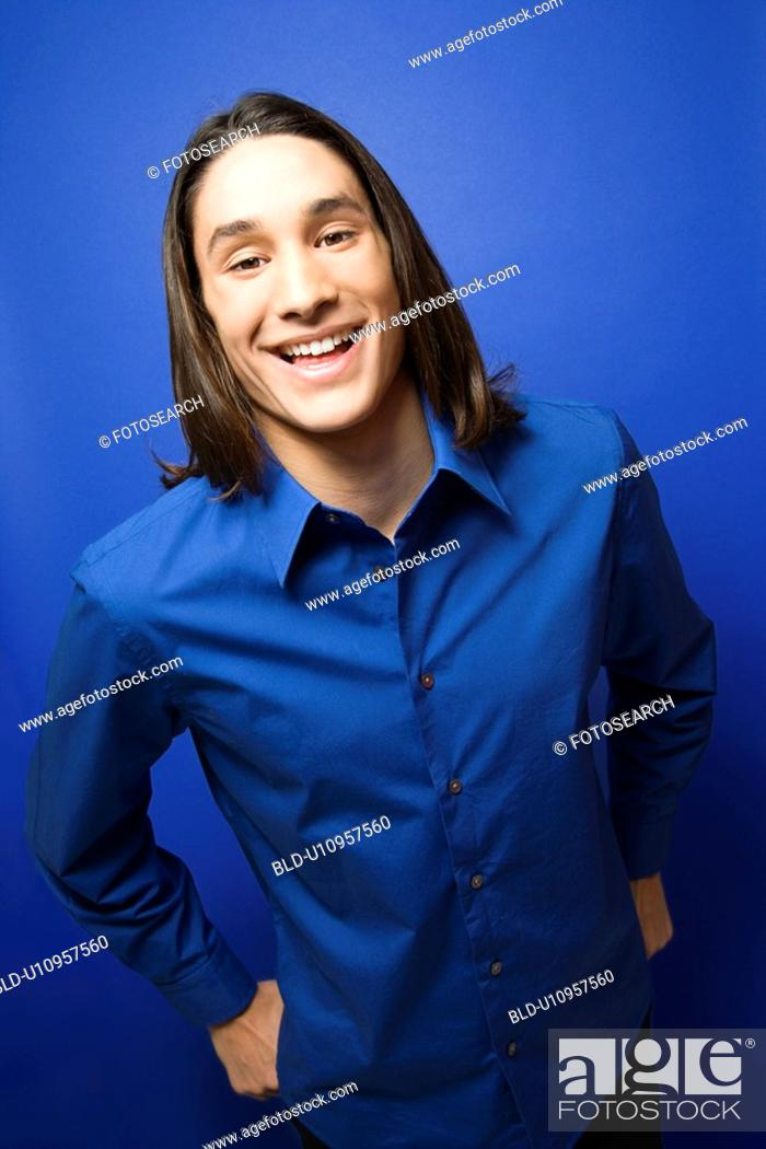 Stock Photo: Portrait of Asian-American teen boy smiling at camera against blue background.