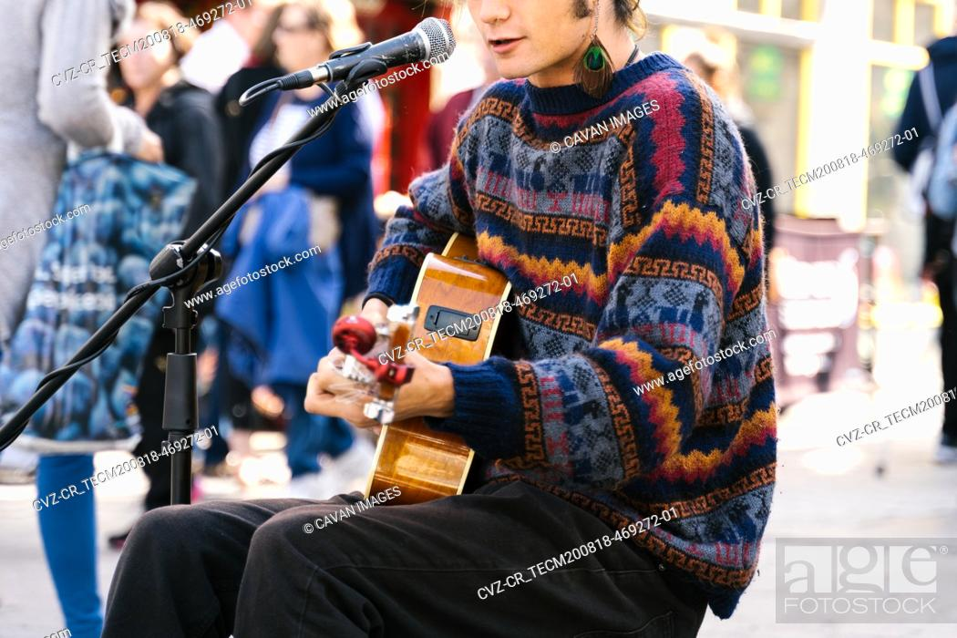 Imagen: Selective focus on the lips of a young man singing while playing guitar in the street.