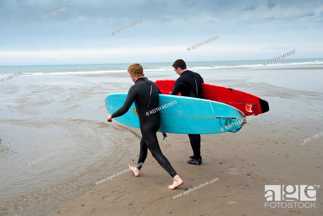Stock Photo: Two men carrying their surfoards, Borth , Ceredigion, West Wales UK.