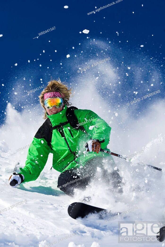 Stock Photo: A skier skis hard through the exploding powder snow.