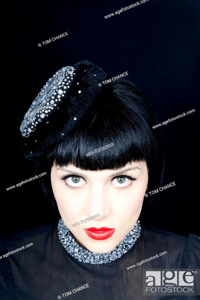 Stock Photo: Close up of young woman against black background.