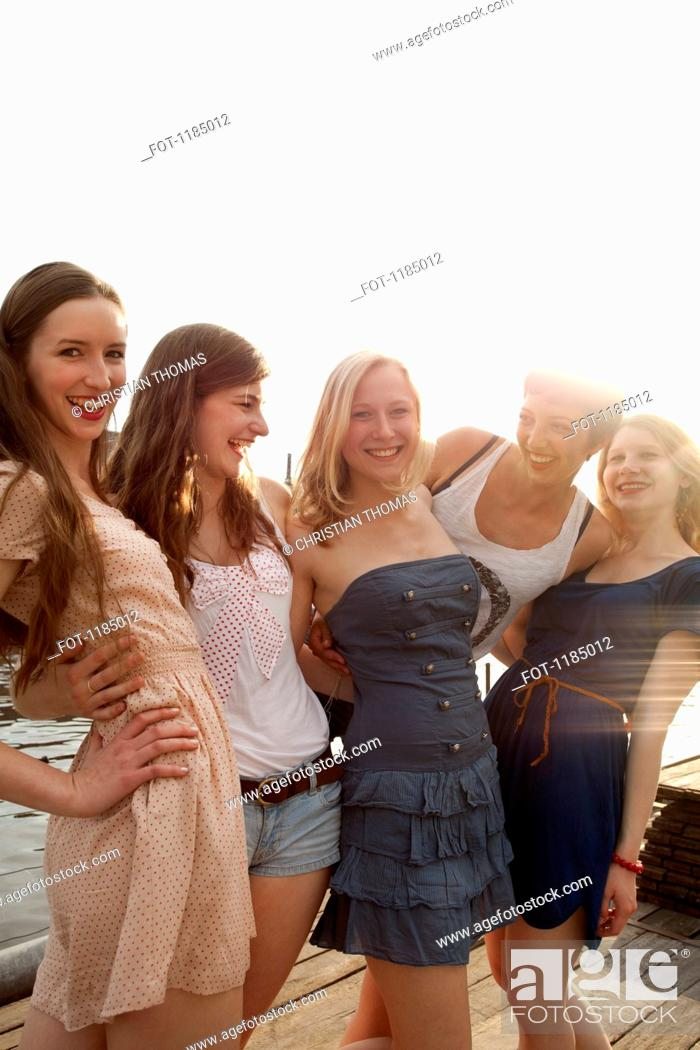 Stock Photo: Five young female friends together on a jetty.