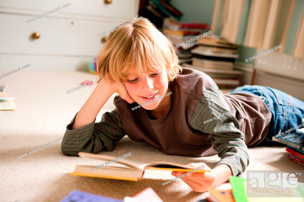 Stock Photo: Young boy lying on his front, reading a book in his bedroom.