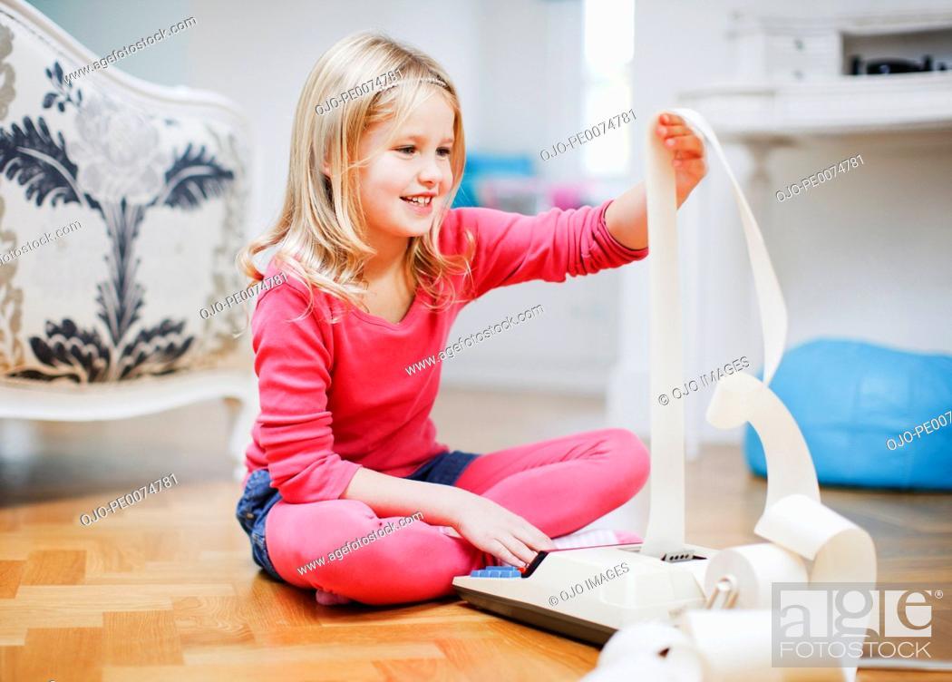 Stock Photo: Girl looking at adding machine tape.