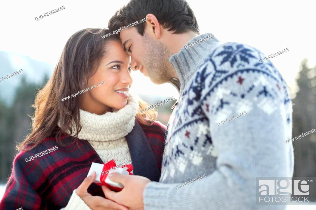 Stock Photo: Smiling couple face to face with Christmas gift.