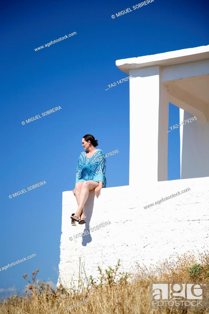 Stock Photo: Woman with blue kaftan sitting on wall in greece.