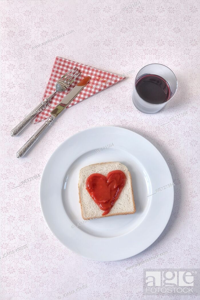 Stock Photo: a slice of toast with a heart of ketchup.