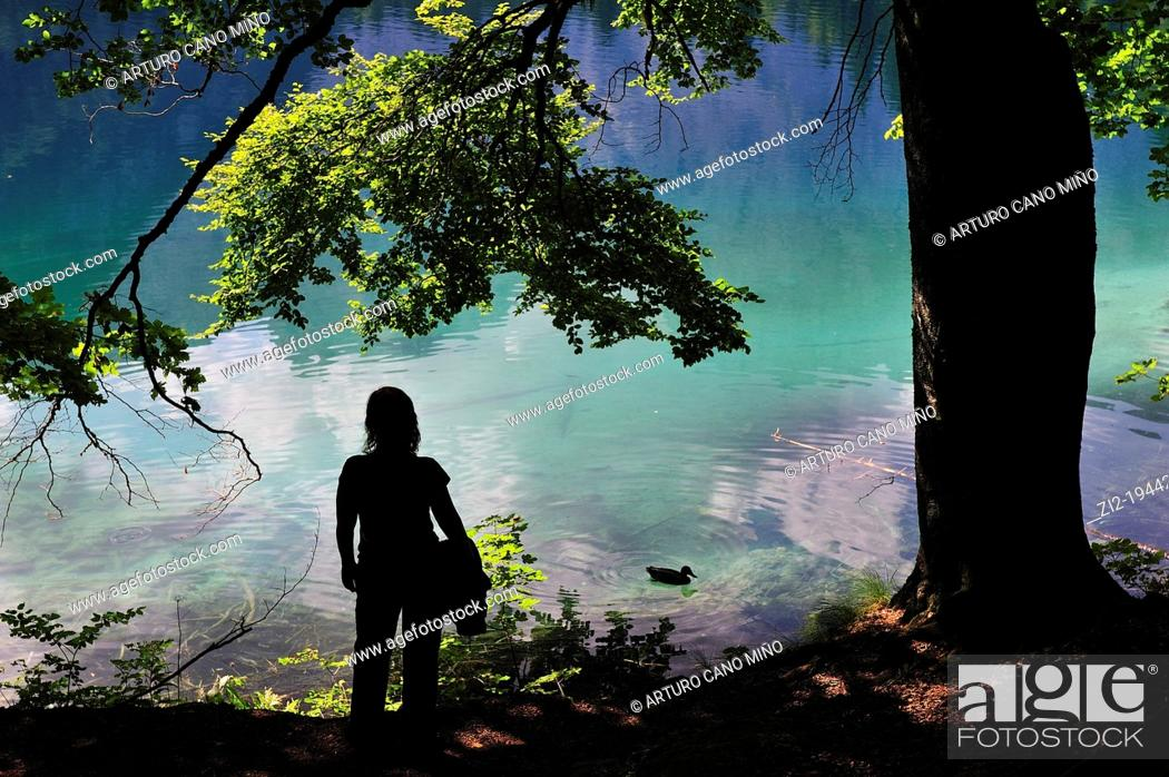 Stock Photo: Girl watching the lake Fusine, Julian Alps. Italy.
