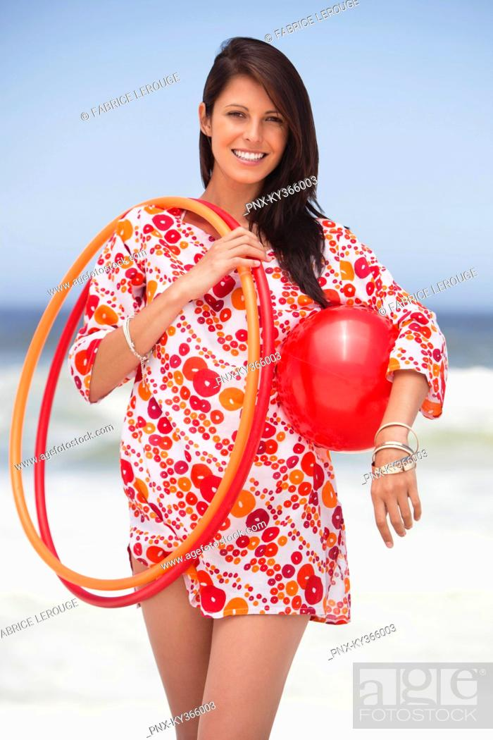 Stock Photo: Portrait of a young woman carrying ball and plastic hoops.