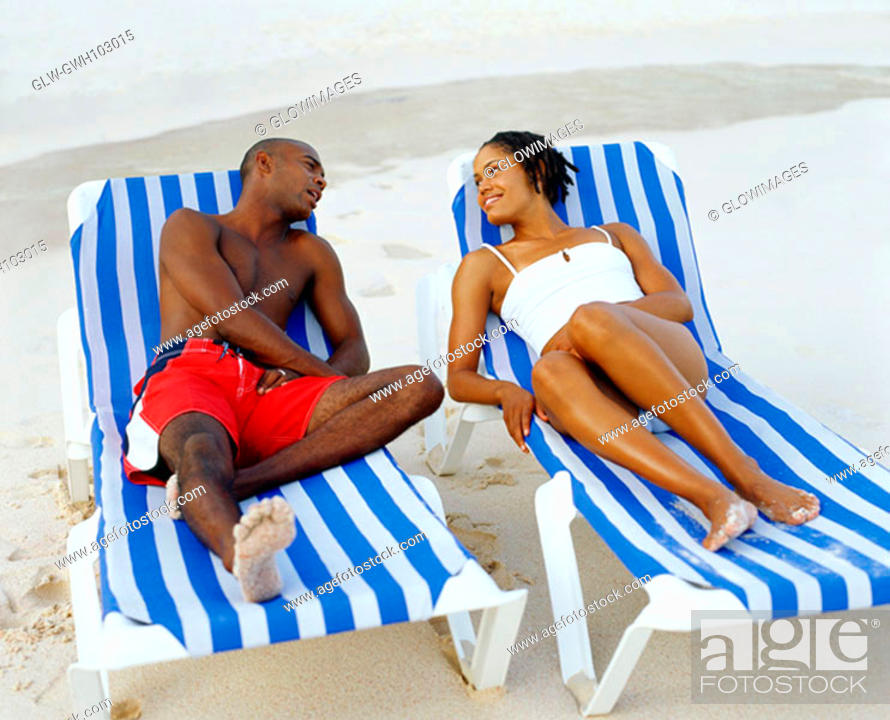 Stock Photo: Young couple lying on lounge chairs and looking at each other, Bermuda.