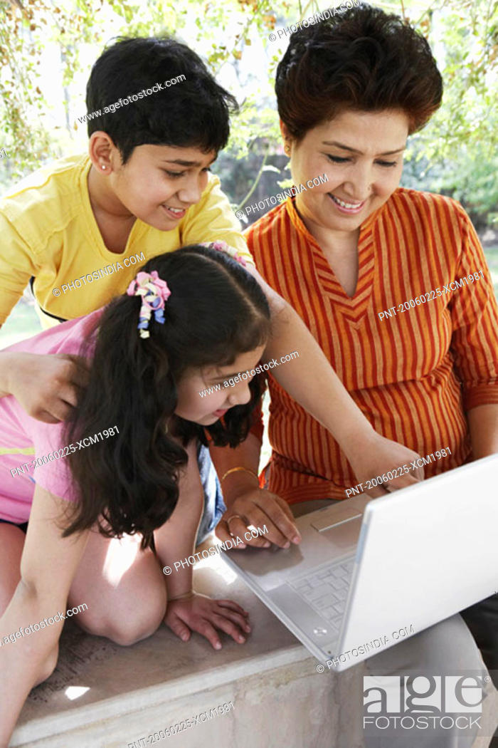 Stock Photo: Close-up of a grandmother and her two grandchildren looking at a laptop.