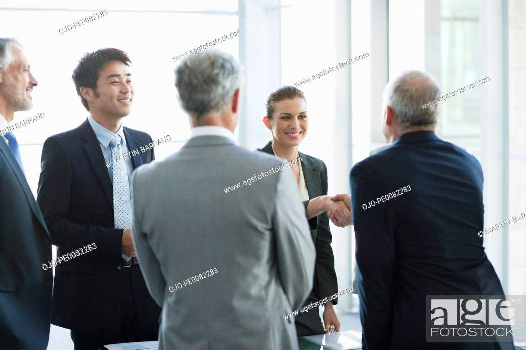 Stock Photo: Business people shaking hands in conference room.